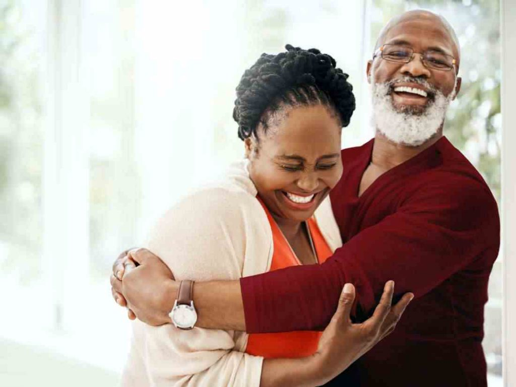 An elderly couple smiling and hugging eachother