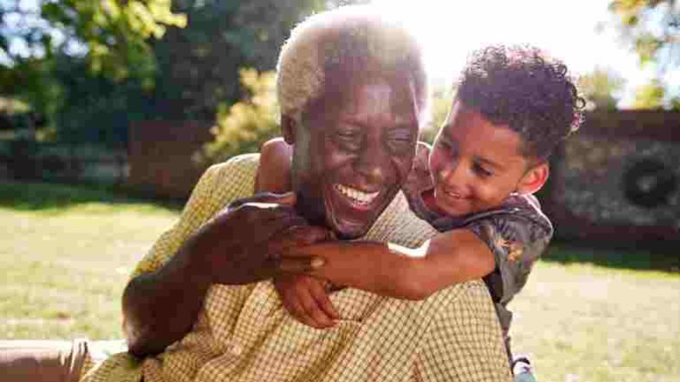 An elderly man giving his grandson a hug and smiling after signing up for a debt management plan
