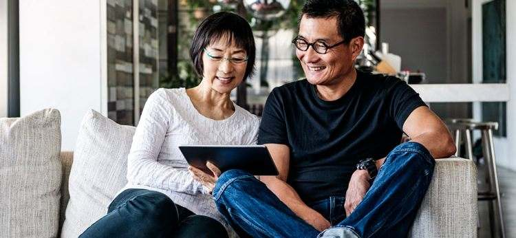 A middle-aged Asian couple smile as they look at their tablet together