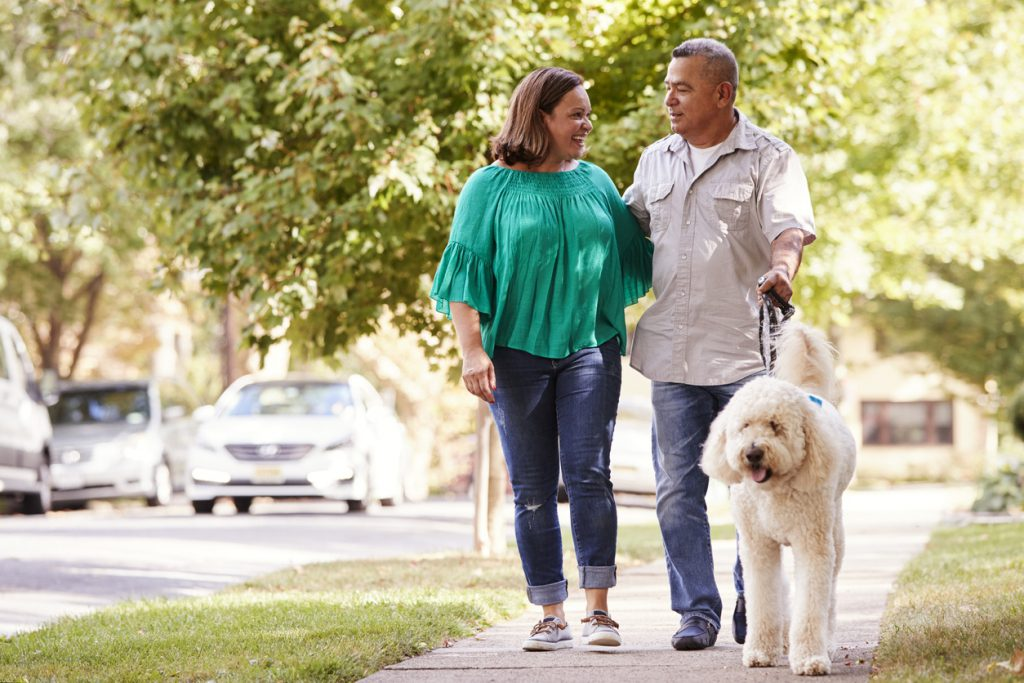 Senior Couple Walking Dog Along Suburban Street after receiving first time home buyer counseling