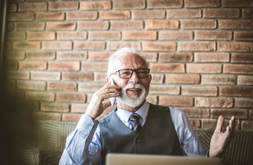 An elderly business man smiling as he talks on the phone